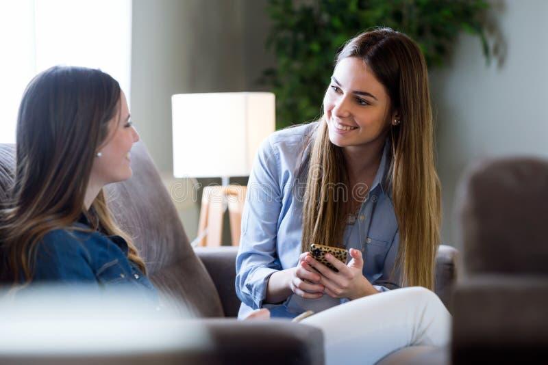 Zwei glückliche junge Freundinnen, die sich zu Hause im Wohnzimmer unterhalten stockbilder