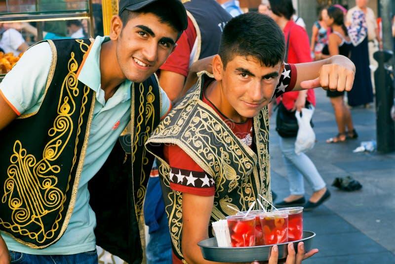 Zwei glückliche junge Verkäufer, die Getränke verkaufen lizenzfreie stockfotos