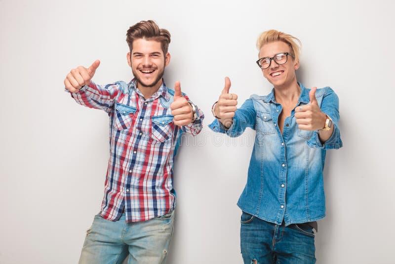 Zwei glückliche junge zufällige Männer, die das okayzeichen machen lizenzfreie stockfotos