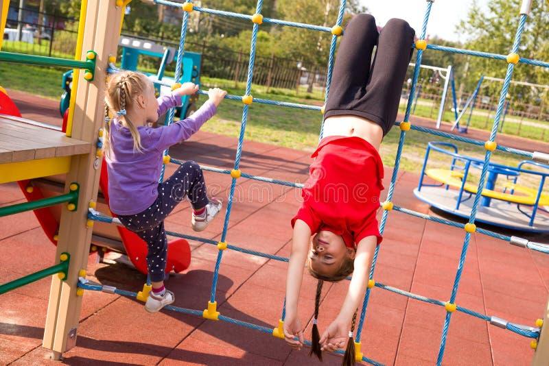 Zwei glückliche kaukasische Mädchen, die Spaß auf dem Spielplatz, das Seilnetz kletternd haben lizenzfreies stockbild