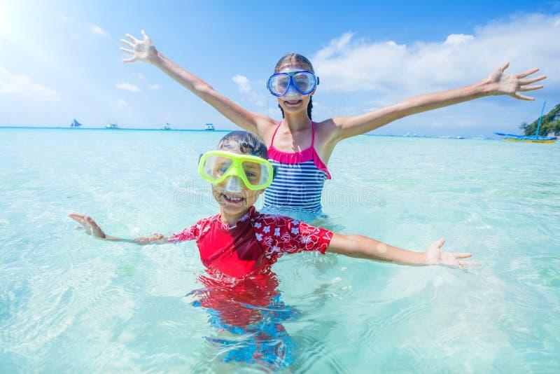 Zwei glückliche Kinder in den Tauchmasken, die Spaß auf dem Strand haben lizenzfreie stockfotografie