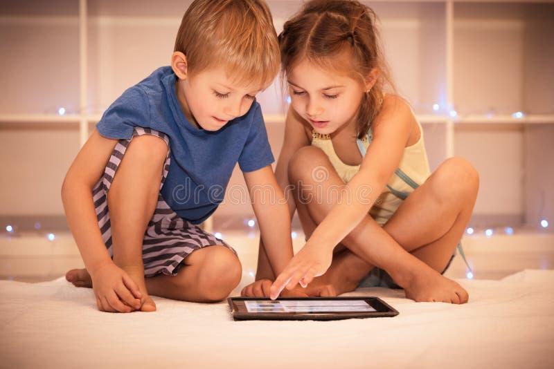 Zwei glückliche Kinder, die auf der Tablette spielen lizenzfreie stockfotos