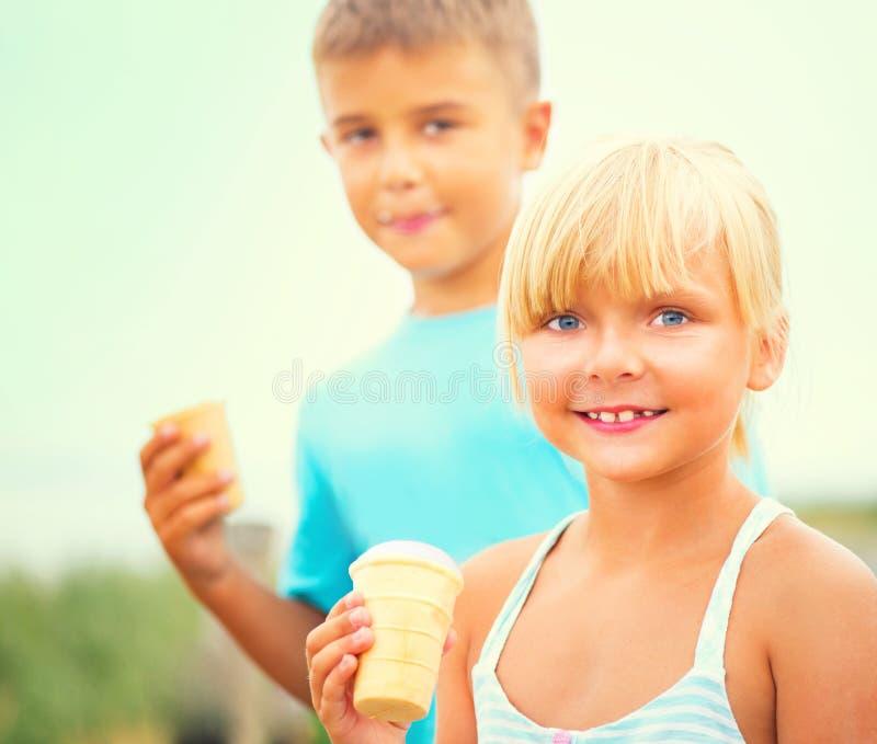 Zwei glückliche Kinder, die draußen Eiscreme essen lizenzfreie stockbilder