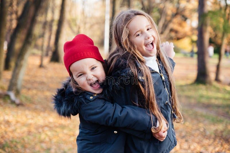 Zwei glückliche Kinder, die im Herbstpark, Lächeln, Kamera betrachtend umarmen Nette stilvolle Kinder, die modische Ausstattung i lizenzfreie stockbilder