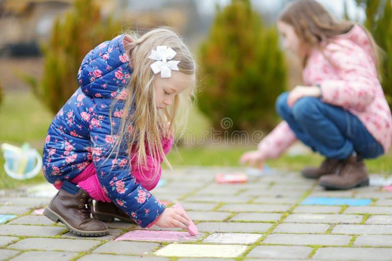 Zwei glückliche Kinder, die mit bunten Kreiden auf einem Bürgersteig zeichnen Sommertätigkeit für kleine Kinder lizenzfreie stockbilder
