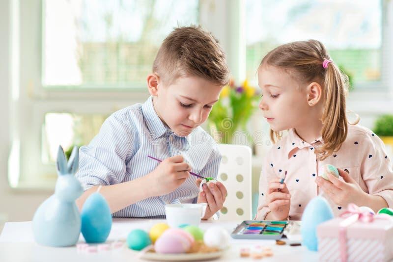 Zwei glückliche Kinder, die Spaß während der Malerei haben, ärgert für Ostern herein lizenzfreies stockbild