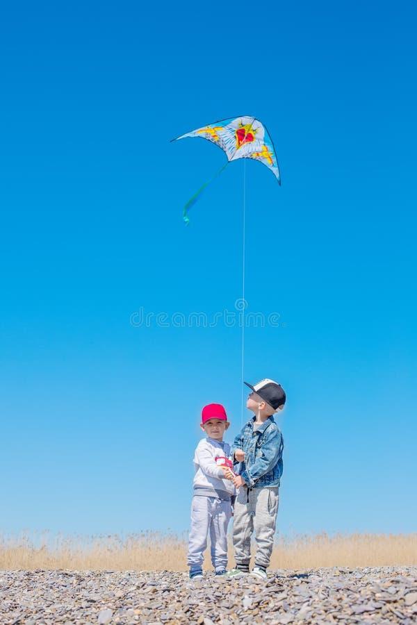 Zwei glückliche Kinder mit einem Drachen lizenzfreie stockfotos