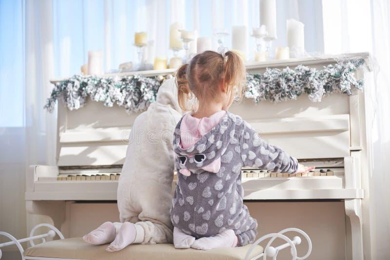 Zwei glückliche kleine Mädchen in den Pyjamas spielen das Klavier am Weihnachtstag lizenzfreie stockfotos