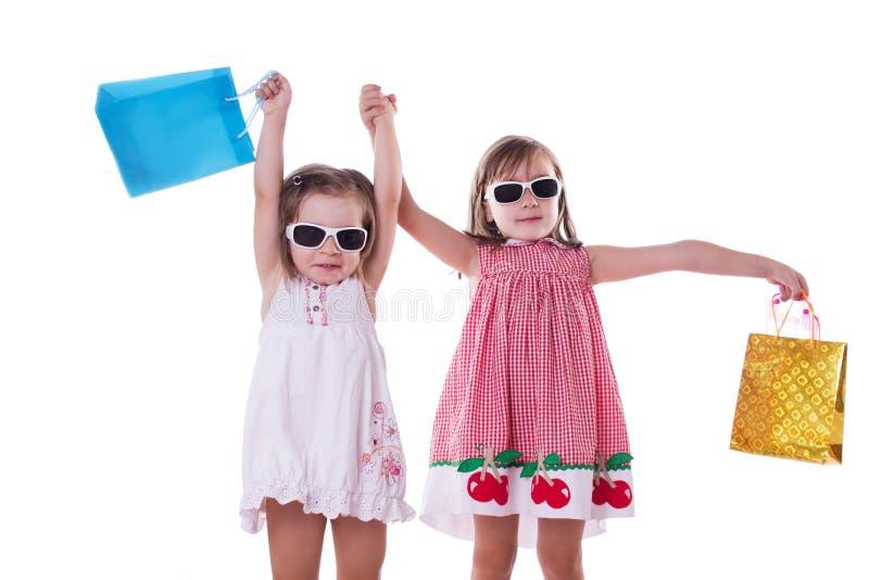 Zwei glückliche kleine Mädchen in den Sonnenbrillen und in den Einkaufstaschen lizenzfreie stockfotos