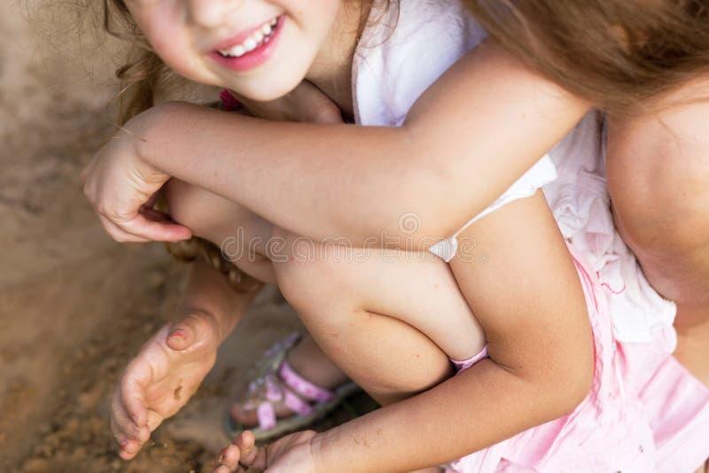 Zwei glückliche kleine Mädchen, die an der Sommergleichheit lachen und umfassen stockbilder