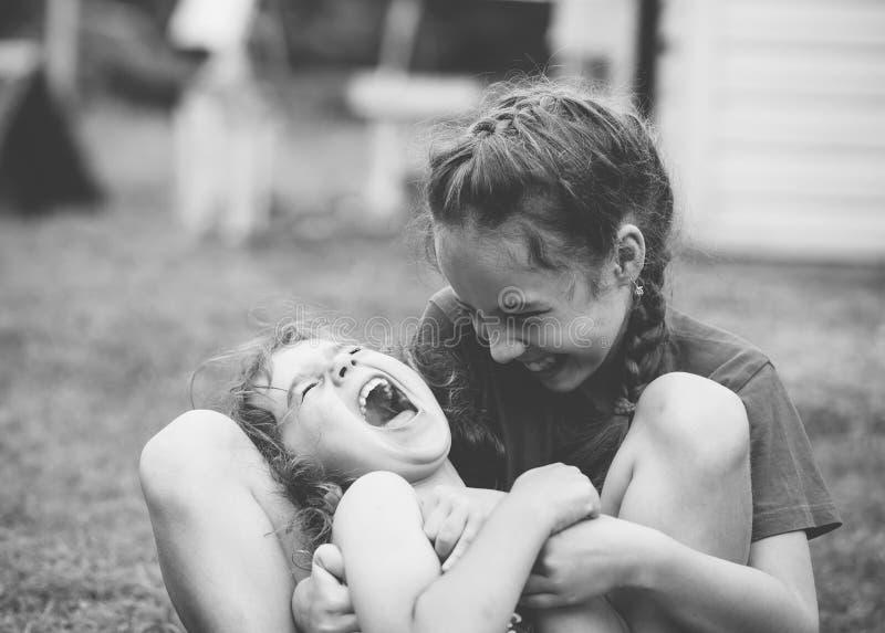 Zwei glückliche kleine Mädchen, die am Sommerpark lachen und umarmen stockbilder
