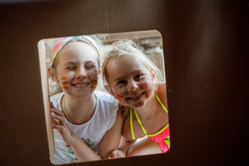 Zwei glückliche kleine Schwestern schaut durch Fenster des Papphauses lizenzfreie stockfotos