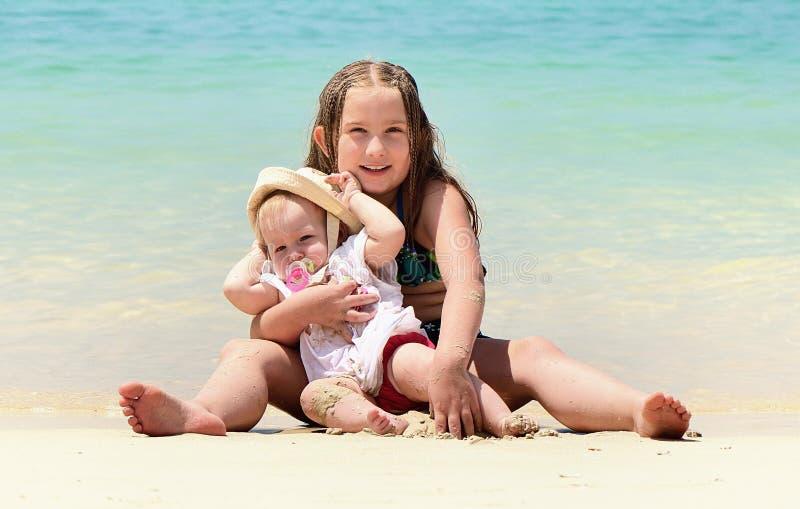 Zwei glückliche lächelnde Schwestern, die auf einem tropischen Strand sitzen stockfoto