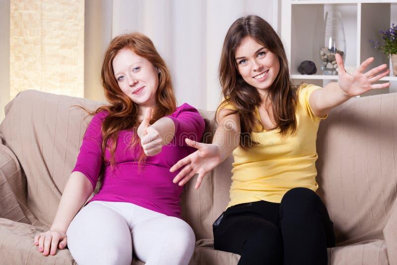Zwei glückliche Mädchen auf einer Couch lizenzfreies stockbild