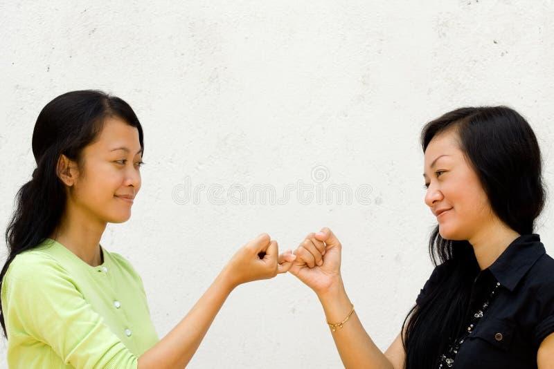 Zwei glückliche Mädchen bilden Frieden miteinander stockbild