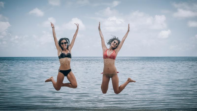 Zwei glückliche Mädchen, die auf einen tropischen Strand springen stockbild