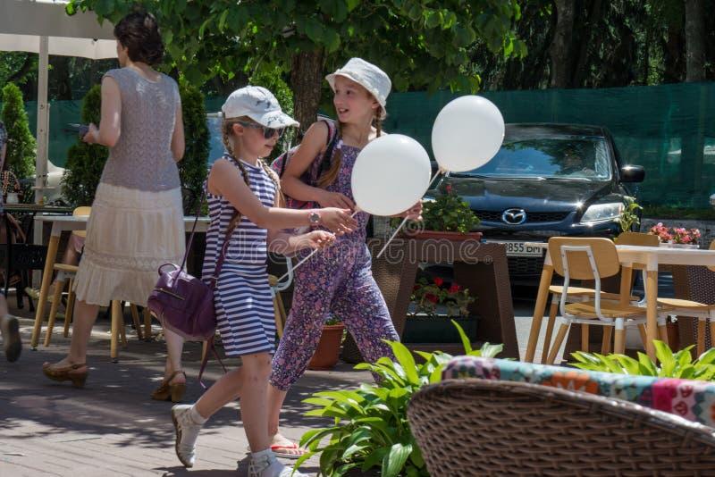 Zwei glückliche Mädchen, die auf Straße mit baloons während des Kinderschutztages gehen lizenzfreies stockfoto