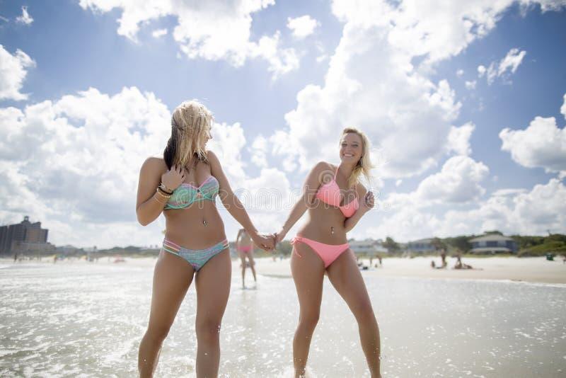 Zwei glückliche Mädchen, die im Meer stehen stockfotografie