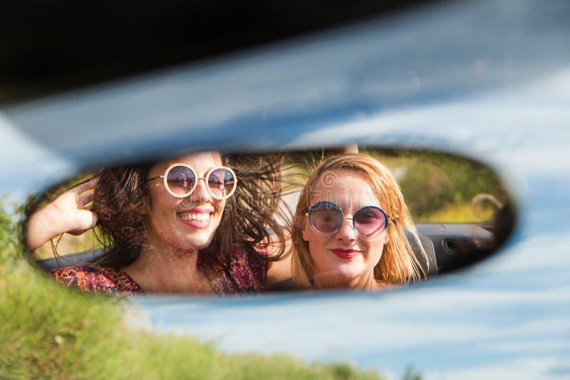 Zwei glückliche Mädchen in einem Autorückspiegel stockbild
