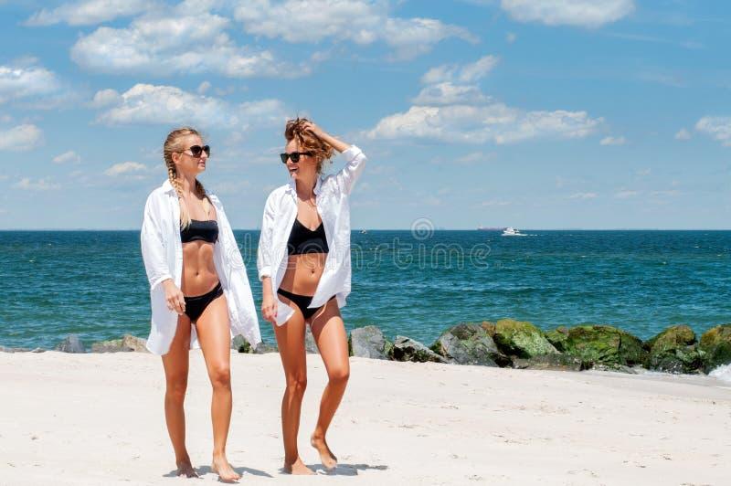Zwei glückliche Mädchen im Bikini auf dem Strand Beste Freunde, die Spaß, Sommerferien-Feiertag Lebensstil haben lizenzfreie stockbilder
