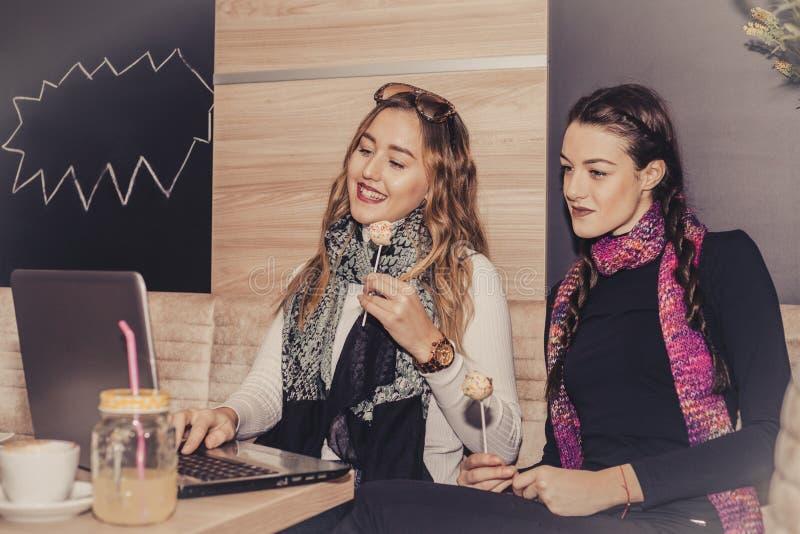 Zwei glückliche Mädchen mit Kuchen unter Verwendung des Laptops und des trinkenden Kaffees in c stockbilder