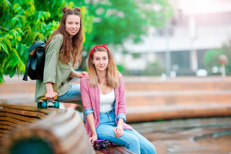 Zwei glückliche Mädchen mit Skateboards draußen Aktive sportliche Frauen, die Spaß zusammen im Rochenpark haben stockfotos