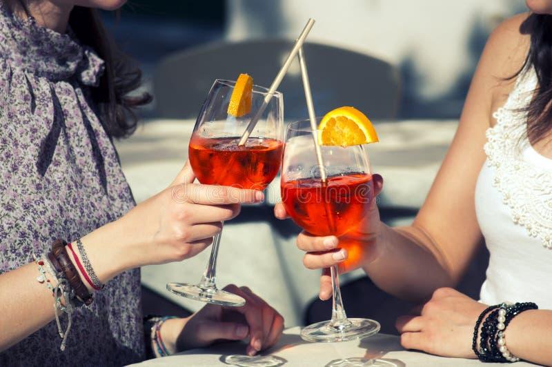 Zwei glückliche Mädchen, während sie ein Cocktail trinken stockfoto