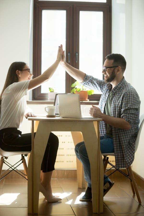 Zwei glückliche Mitarbeiter, die hohe fives auf Geschäftstreffen geben lizenzfreies stockfoto