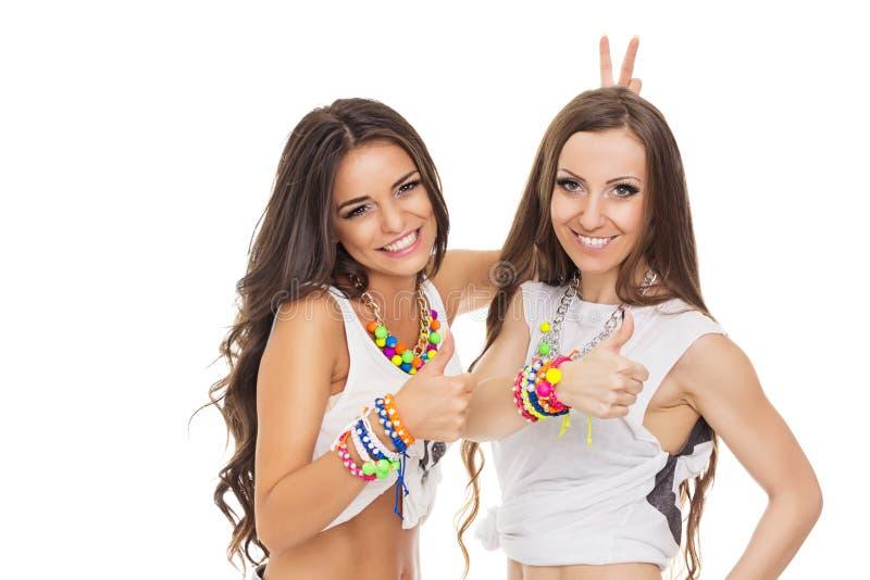 Zwei glückliche moderne junge Frauen, welche die Daumen oben tragen bunten Schmuck zeigen lizenzfreies stockfoto