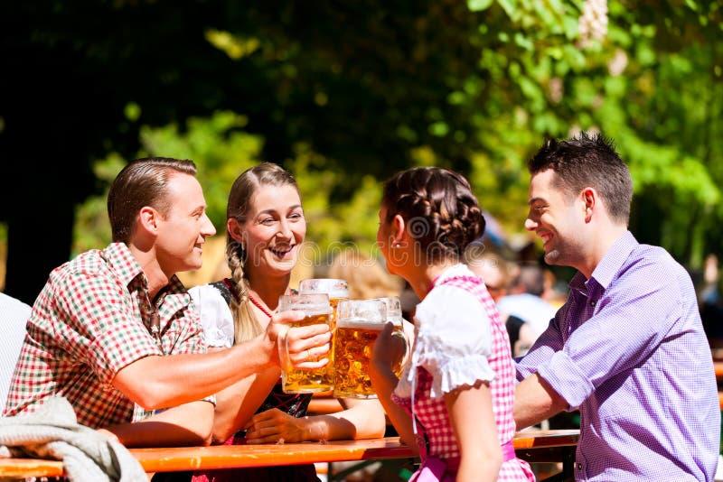 Zwei glückliche Paare, die im Biergarten sitzen lizenzfreies stockbild