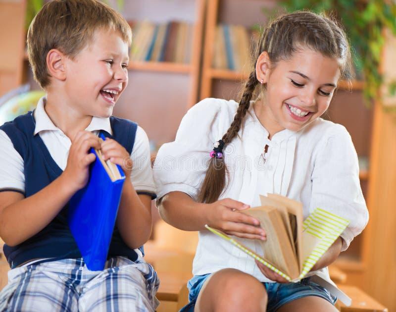 Zwei glückliche Schulkinder haben Spaß im Klassenzimmer stockbilder