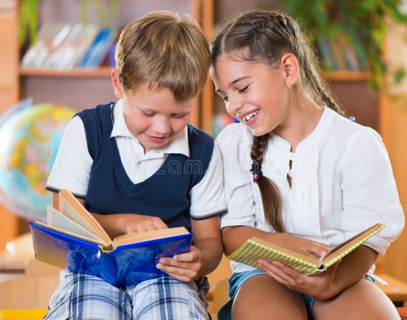Zwei glückliche Schulkinder haben Spaß im Klassenzimmer lizenzfreies stockbild