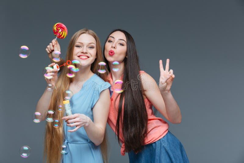 Zwei glückliche spielerische junge Frauen mit Schlagblasen des bunten Lutschers lizenzfreie stockbilder