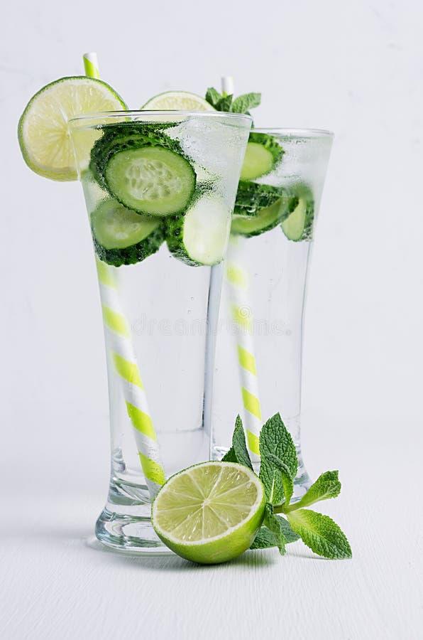 Zwei Glas mit kaltem Detoxwasser mit Scheiben Gurke, Kalk, Minze, Eis, Stroh auf weißer hölzerner Planke lizenzfreie stockfotos