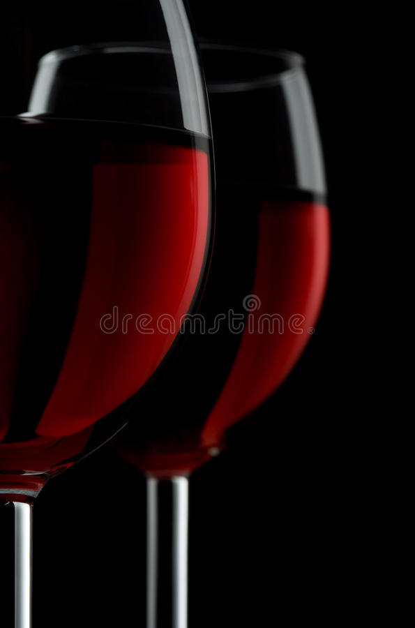 Zwei glassed vom Rotwein, der auf schwarzem Hintergrund getrennt wurde lizenzfreie stockfotografie