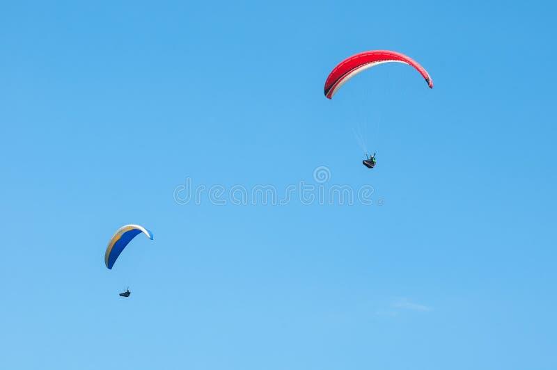 Zwei Gleitschirme, die in den blauen Himmel fliegen lizenzfreies stockbild