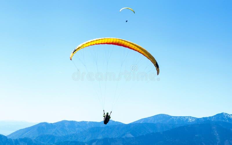 Zwei Gleitschirme, die im Himmel über den blauen Bergen ansteigen lizenzfreie stockfotos