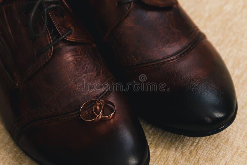 Zwei Goldbreite Eheringe, gelegen auf den Schuhen der Männer machten vom braunen Leder lizenzfreies stockbild