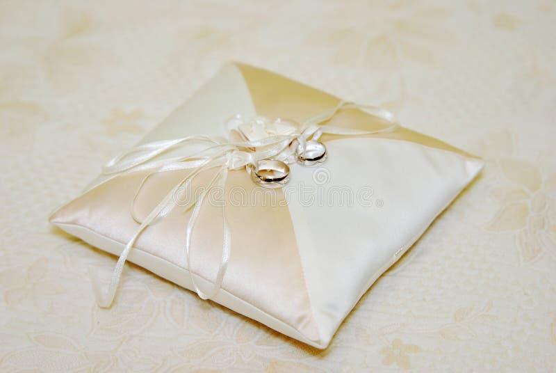 Zwei Goldeheringe auf weißer Spitzeauflage stockfotografie