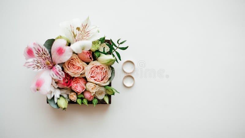 Zwei goldene Eheringe vereinbarten nahe schöner und netter Blumenzusammensetzung in einem kleinen Kasten lizenzfreie stockfotografie