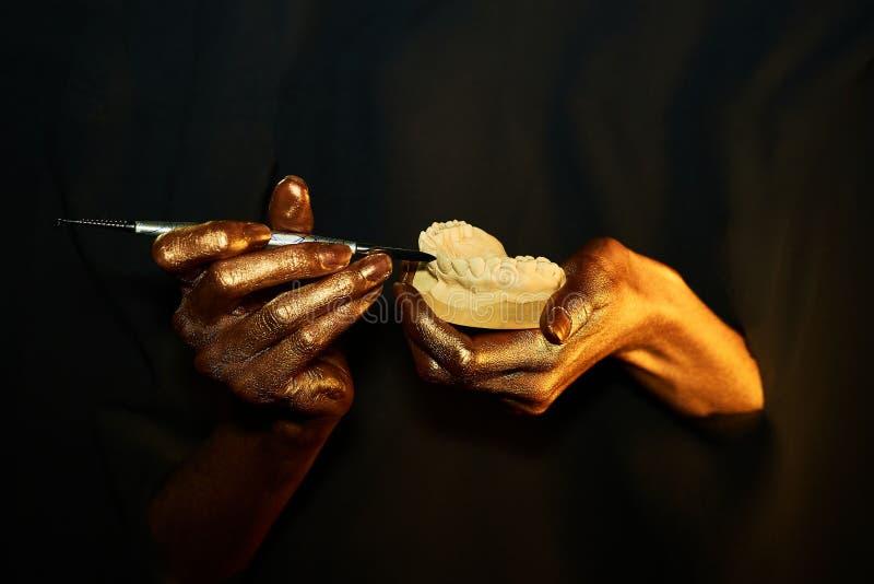 Zwei goldene Hände mit einem zahnmedizinischen Instrument auf einem schwarzen Hintergrund stockfotos