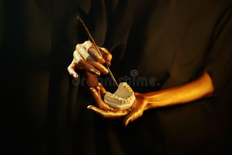Zwei goldene Hände mit einem zahnmedizinischen Instrument auf einem schwarzen Hintergrund lizenzfreie stockbilder
