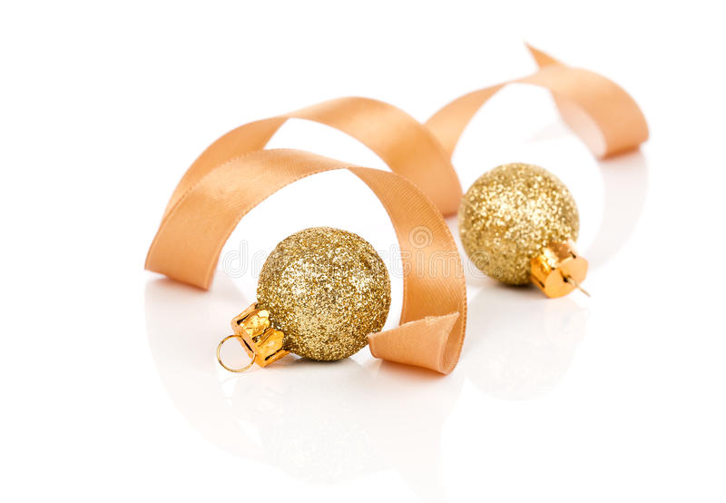 Zwei goldene Weihnachtsdekorationsbälle mit Satinband lizenzfreie stockfotos