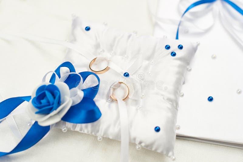Zwei Goldringe auf einer weißen Kissenauflage Das Konzept der Einheits- und Hochzeitsfeier stockfotos