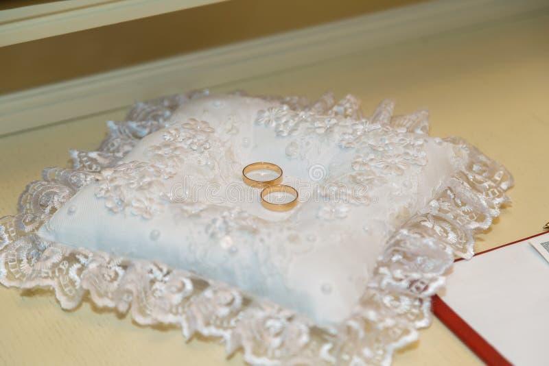 Zwei Goldringe auf einer weißen Kissenauflage Das Konzept der Einheits- und Hochzeitsfeier lizenzfreie stockfotos