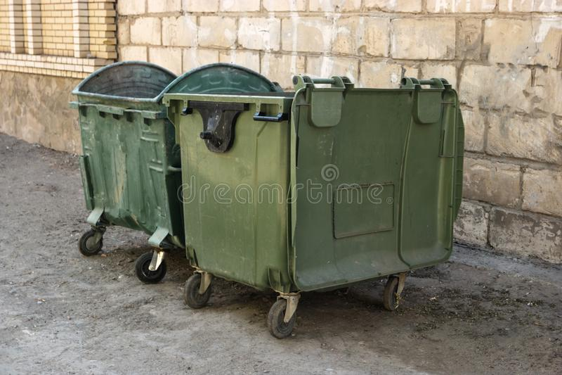 Zwei grüne Abfall-Müllcontainer in der Front Of White Brick Wall-Winkelsicht Grüne Wiederverwertungsmüllcontainer gegen eine Back stockbild