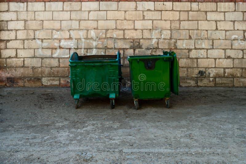 Zwei grüne Abfall-Müllcontainer in Text Front Of White Brick Walls Front View With Room For Zwei Metallmüllcontainerdosen auf der lizenzfreie stockfotografie