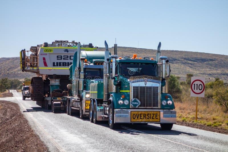 Zwei grüne schwere LKWs Kenworth T327 der Gebührnfirma, die extrem schwere Überformatlast auf den Straßen in West transportiert stockfoto
