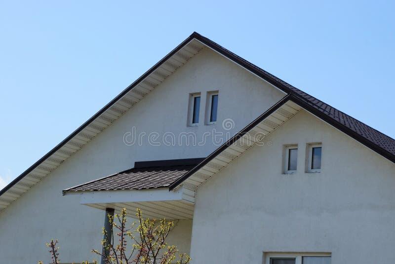 Zwei graue Dachböden mit Fenstern gegen einen blauen Himmel lizenzfreie stockfotos