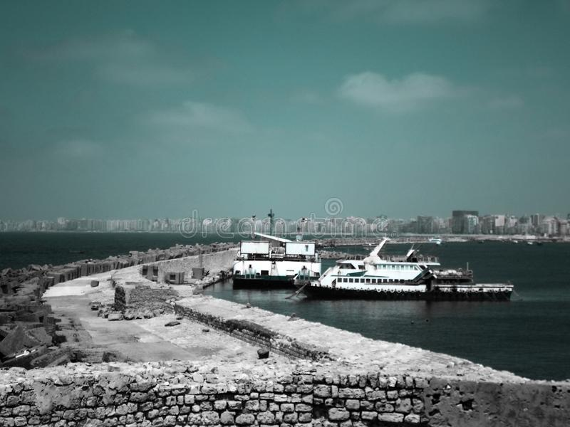 Zwei große Fischboote, die nahe bei den Wänden der Zitadelle von Qaitbay auf der Küste von Alexanderia, Ägypten parken lizenzfreies stockbild